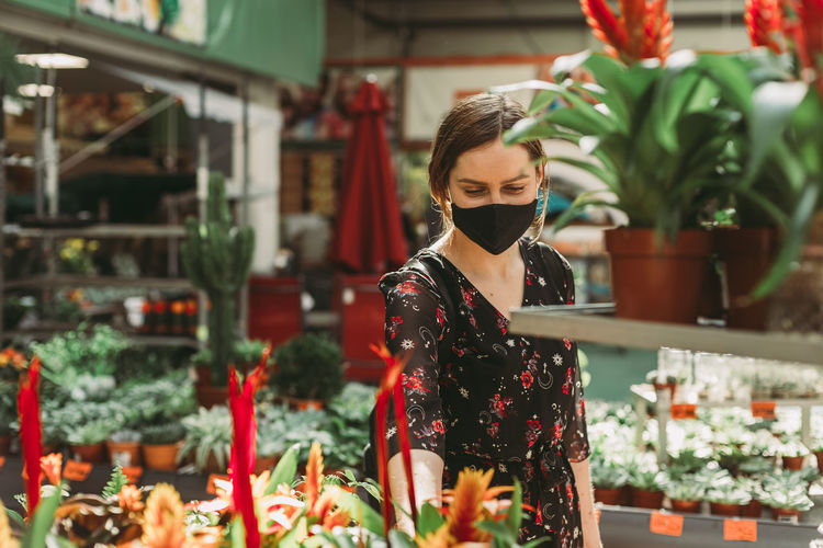Portrait of woman standing by potted plants at store