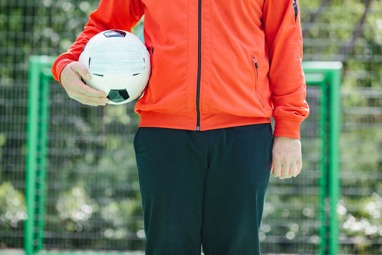 Midsection of man holding ball while standing against blurred background