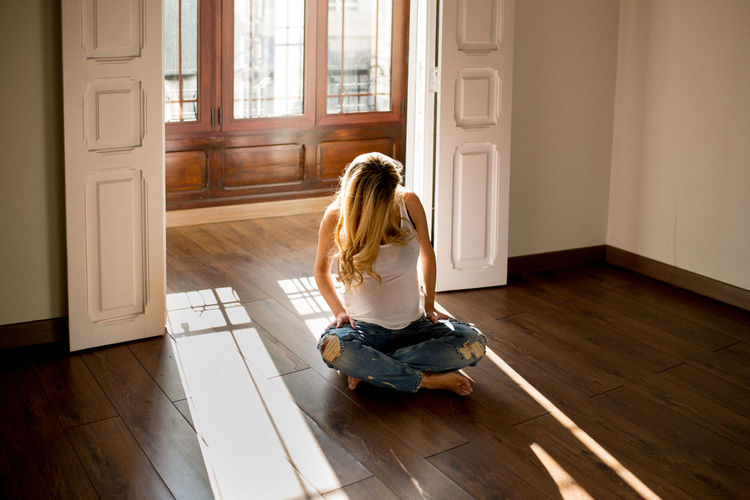 Rear view of woman sitting on floor at home