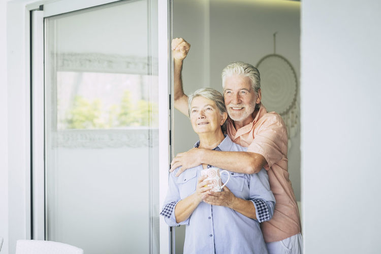 Thoughtful senior couple standing at window at home