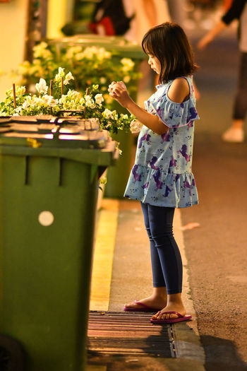 Side view full length of girl standing by garbage can at night
