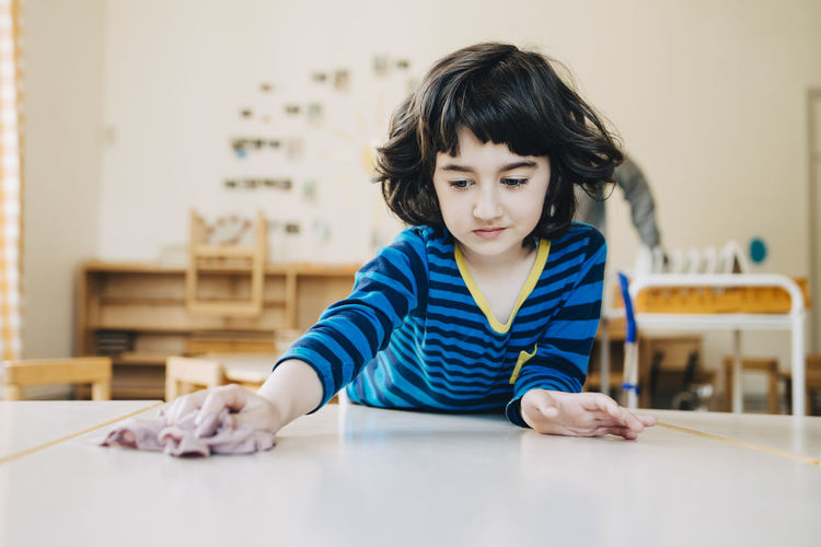 Portrait of boy holding camera on table