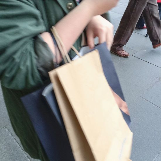 Person walking past with carrier bags hung on arm Person Walking Past Carrier Bags Hung Hanging Arm Shopping Movement Blur