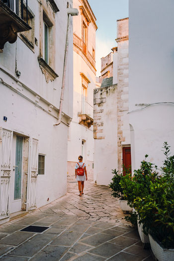 Rear view of woman walking on alley amidst buildings in city