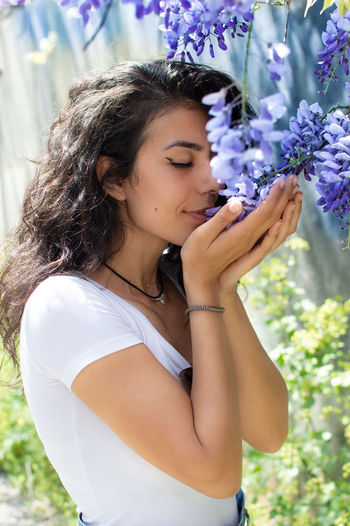 Side view of young woman smelling flowers on plants