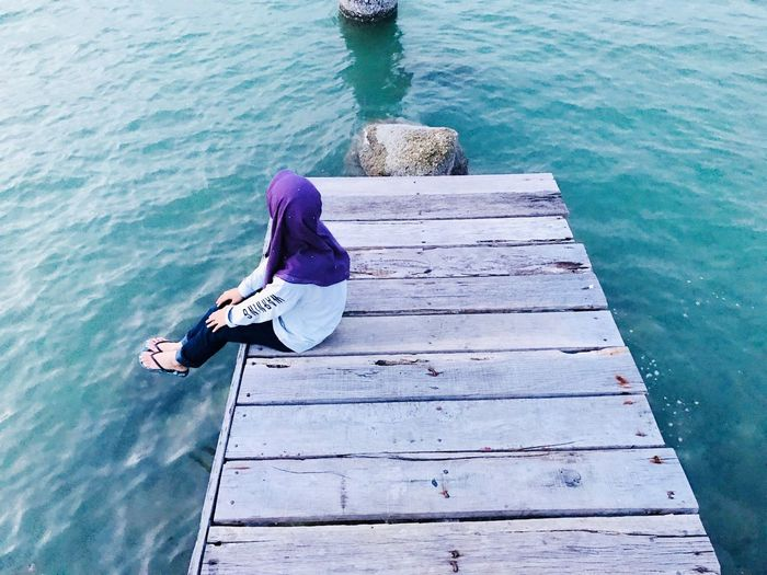 High Angle View Of Woman Sitting On Pier Over Sea
