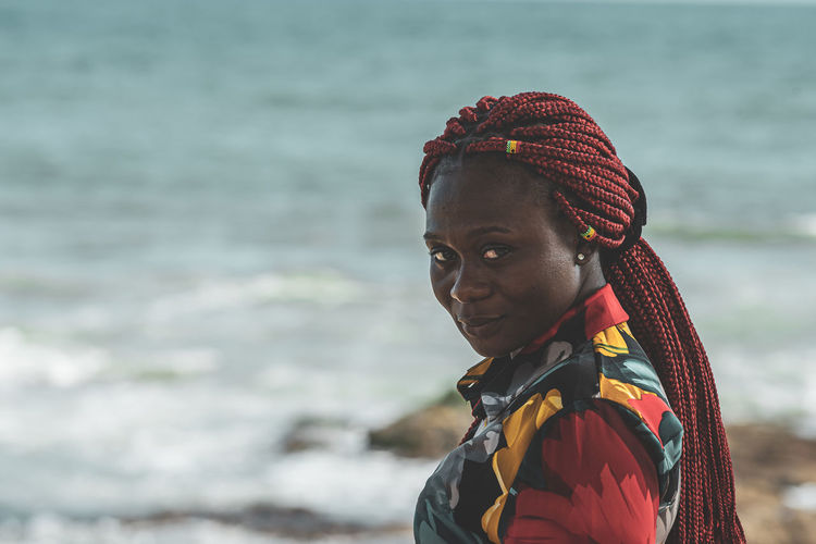 African woman with rasta hair with attached small ghana flags on the accra coast ghana