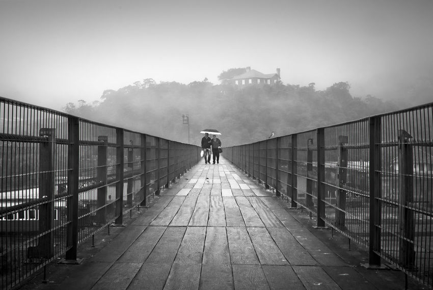 Paranapiacaba Ancient Couple Paranapiacaba São Paulo Brasil Perspective B&w Blackandwhite Bridge Cold Crossing Fence Focus On Foreground Heritage History House Monochrome People Rainy Day Structure Umbrella Village