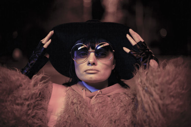 Close-up of woman wearing hat and sunglasses