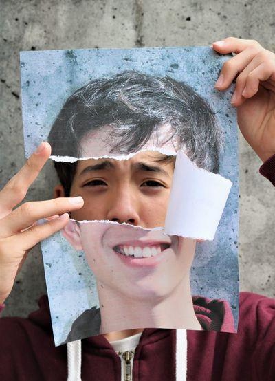 Close-up portrait of boy holding torn portrait