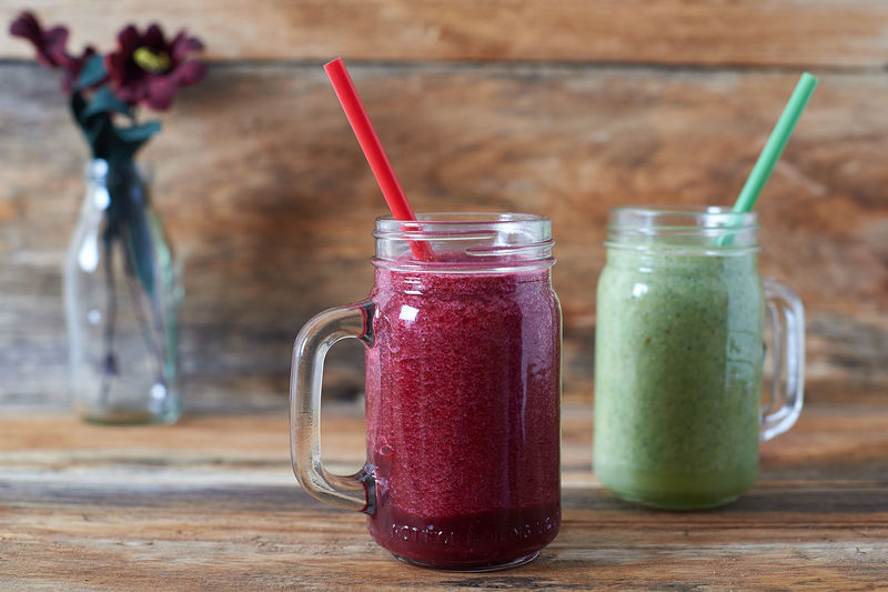 Red and Green Smoothies against a wooden background. Berry Fruit Detox Drink Drinking Straw Drinks Food Food And Drink Food And Drink Foodphotography Freshness Fruit Healthy Eating Indoors  Lifestyles No People Smoothie