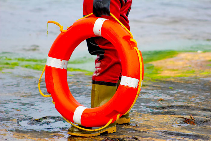 A person holding a life ring pictured from waist down Beach Circle Day Focus On Foreground Geometric Shape Inflatable  Land Life Belt Lifering Nature No People Orange Color Outdoors Protection Red Rescue Safety Safety Equipment Sea Security Tube Water