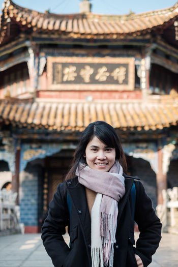Portrait of smiling woman standing against temple