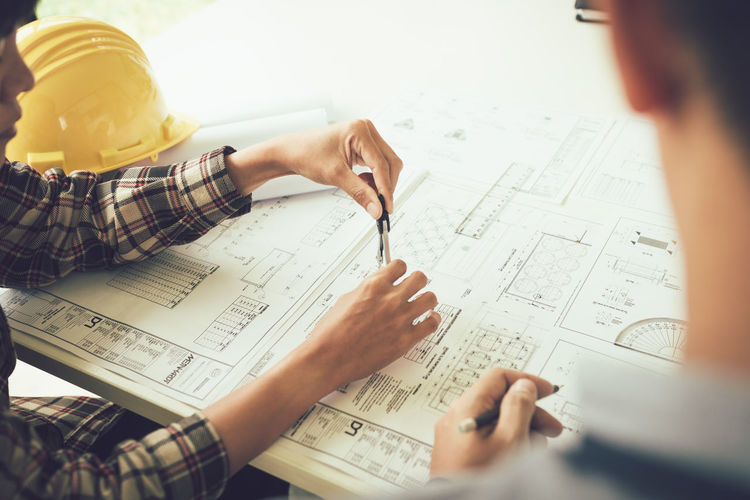 Cropped image of architects working over blueprint at office