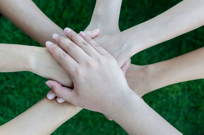 Cropped image of female friends stacking hands over field