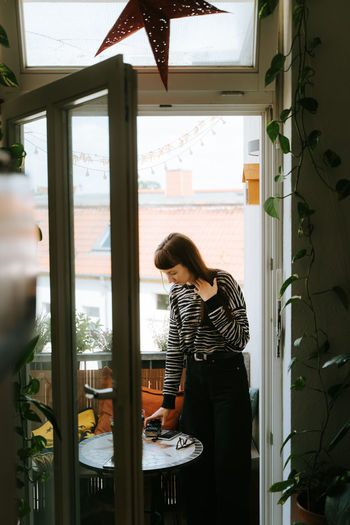Woman standing by window on balcony