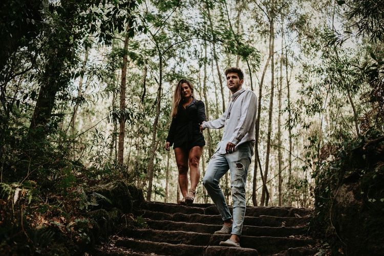Couple Walking Against Trees In Forest