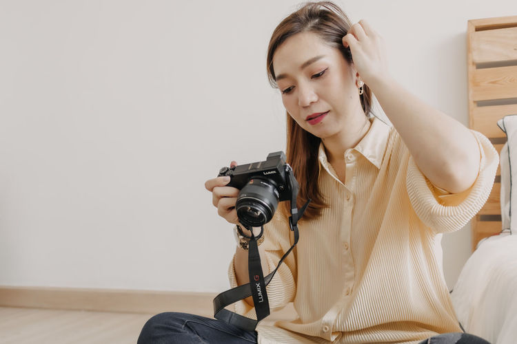 Woman holding camera while sitting at home