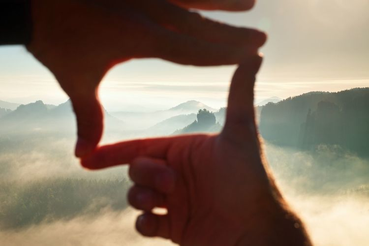 Close up of hands making frame gesture. blue misty valley. sunny spring daybreak in mountains.