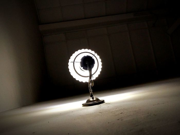 Illuminated electric lamp on wall by building