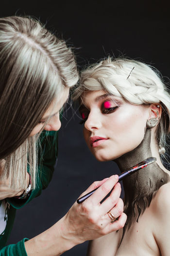 Close-up of artist applying make-up of woman against black background
