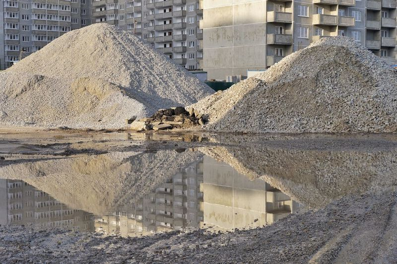 Reflection of construction material on puddle in city