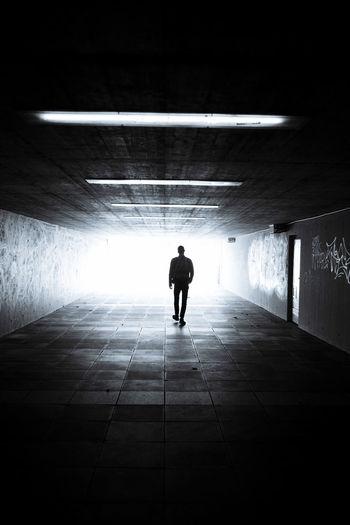 Rear view of silhouette man walking in subway