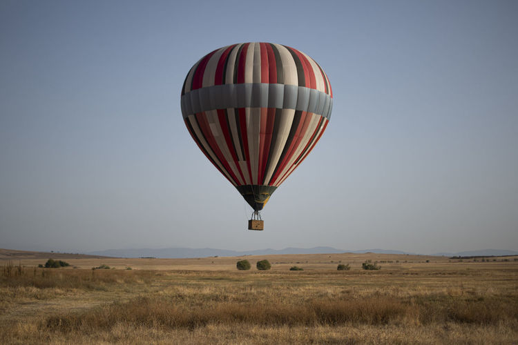 Hot air balloon flying over field against clear sky