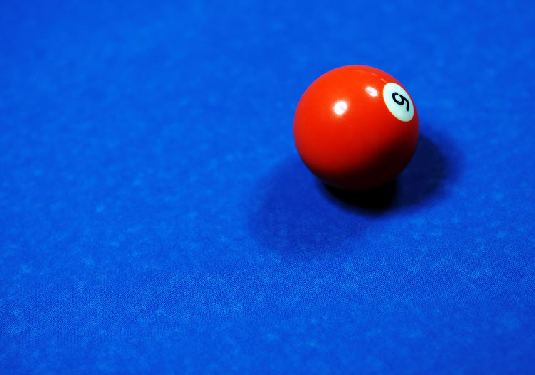 High angle view of number 5 pool ball on blue table