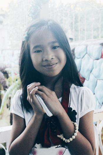 Portrait of smiling girl holding mobile phone