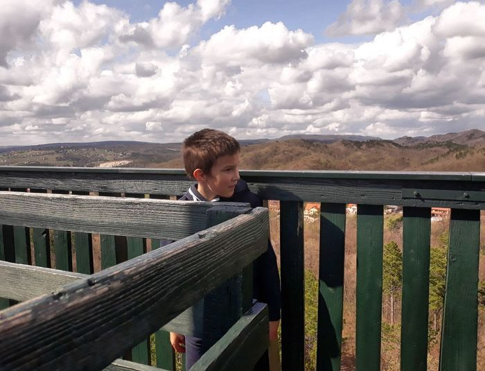 Boy standing by railing against cloudy sky