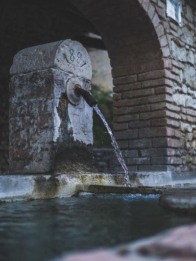 Water fountain against brick wall