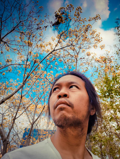 Young man looking away against trees