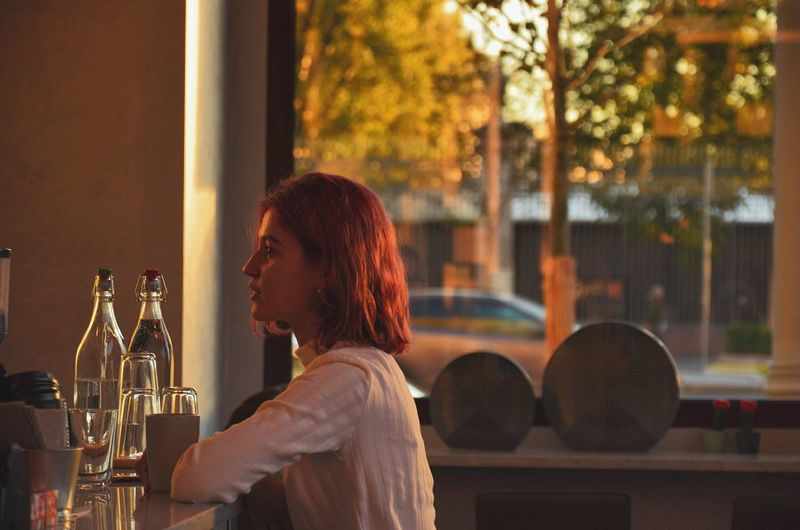 Woman looking away while sitting in bar