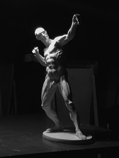 Statue Of Muscular Build Naked Man Against Black Background