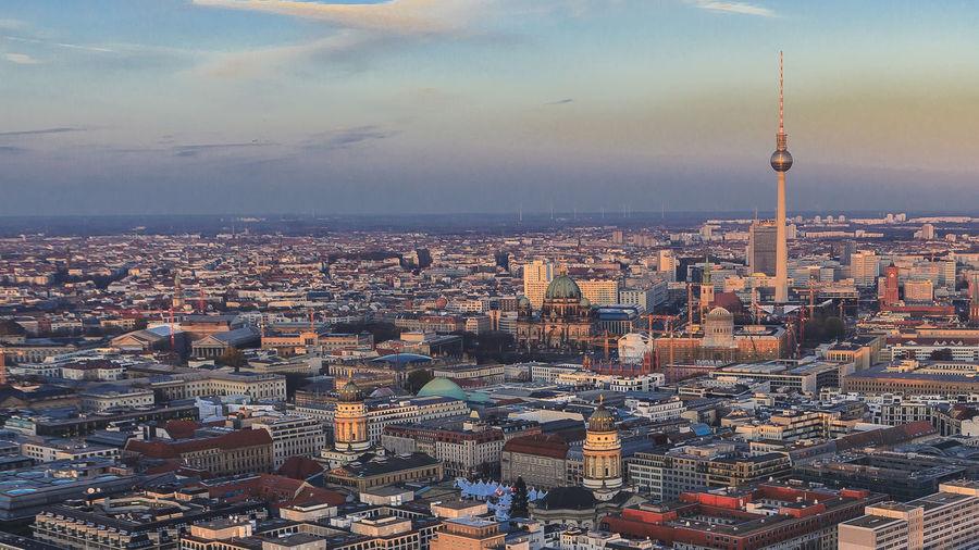 Fernsehturm Amidst Cityscape Against Sky During Sunset