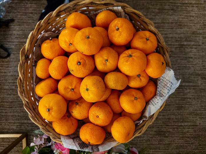 High angle view of orange fruits in basket on table.