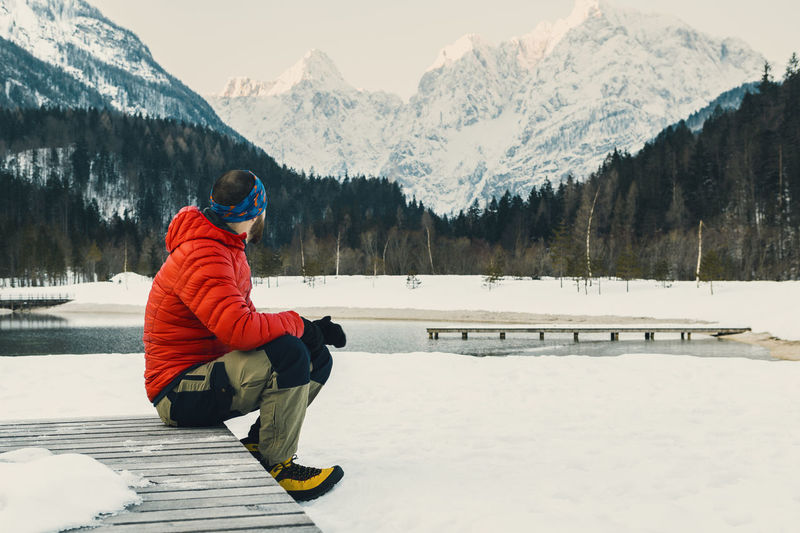 Side view of man sitting at snow covered lakeshore against mountains