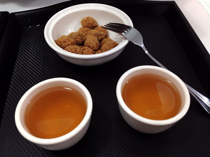 High angle view of black tea with snack on table