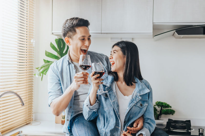 Happy couple holding wineglasses at home