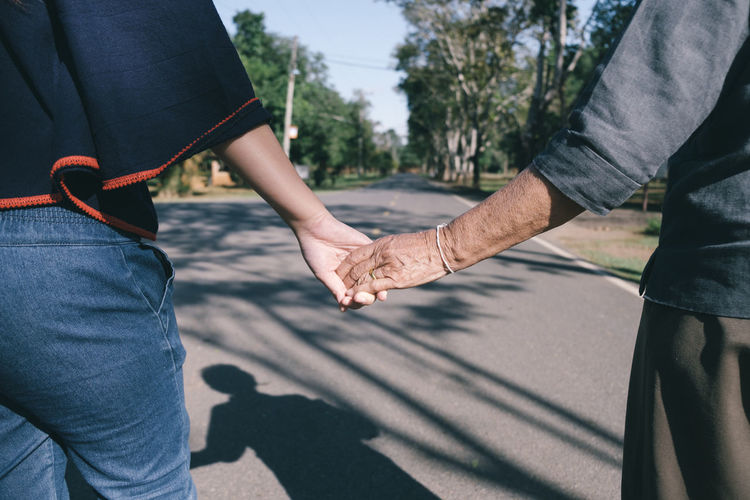 Midsection Of Woman Holding Grandmother Hands On Street