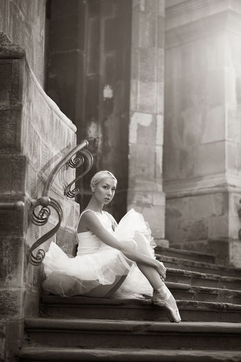 Young woman looking down while sitting on staircase