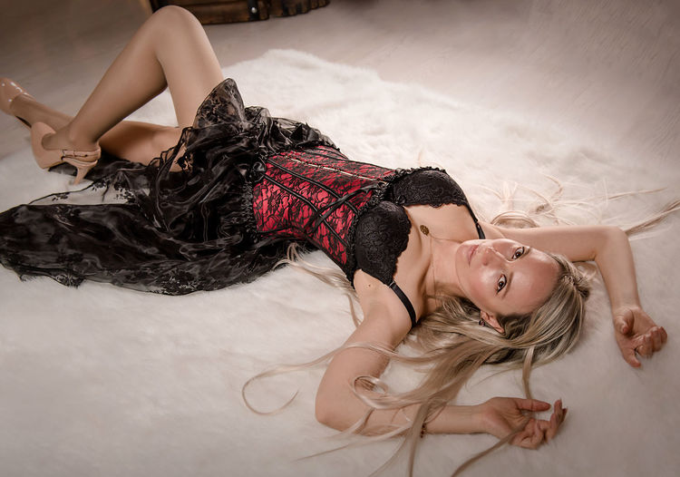 Midsection of woman lying down on bed
