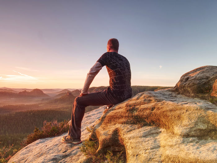 Flare. strong lens defect reflections. man in sportswear is sitting on cliff's edge above valley