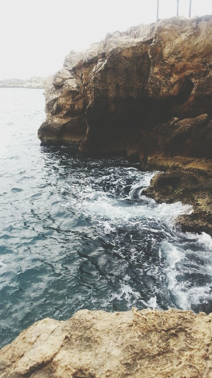 rock - object, sea, water, rock formation, nature, rock, beauty in nature, scenics, wave, day, tranquility, tranquil scene, outdoors, no people, motion, waterfront, beach, cliff, sky, horizon over water