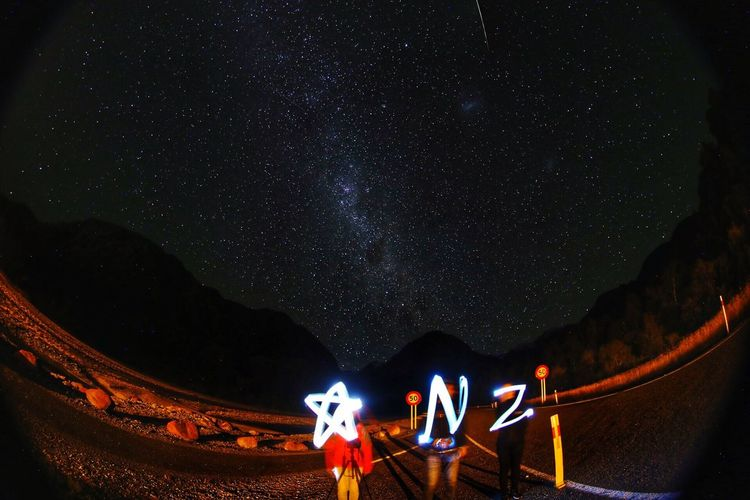 People holding illuminated alphabets against starry sky