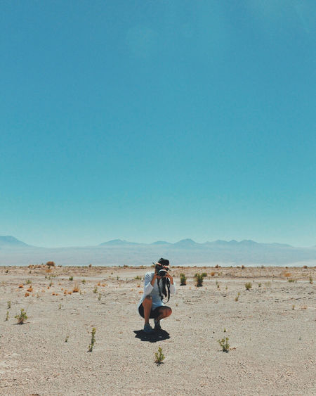 Woman Photographing While Crouching Against Clear Sky At Atacama Desert
