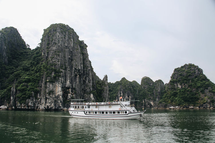 Halong Bay Vietnam Vietnam Beauty In Nature Boat Day Houseboat Longtail Boat Mode Of Transport Mountain Nature Nautical Vessel No People Outdoors Rock - Object Rock Formation Scenics Sky Tranquil Scene Tranquility Transportation Travel Destinations Tree Vacations Water Waterfront