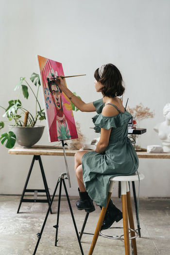 Side view of woman painting on canvas at art studio