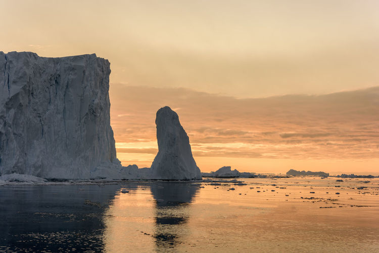Sunset time on Icebergs in Arctic Ocean in Greenland Capture Tomorrow Sunset Sky Water Beauty In Nature Scenics - Nature Sea Tranquility Tranquil Scene Rock Orange Color Rock Formation Idyllic Rock - Object Nature Solid No People Land Non-urban Scene Beach Outdoors Stack Rock